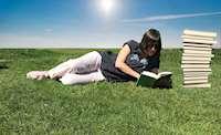 Kvinna ligger på gräset och läser en bok