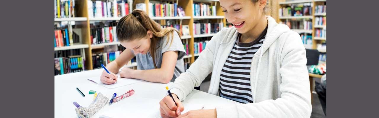 två glada tjejer gör läxor i ett bibliotek